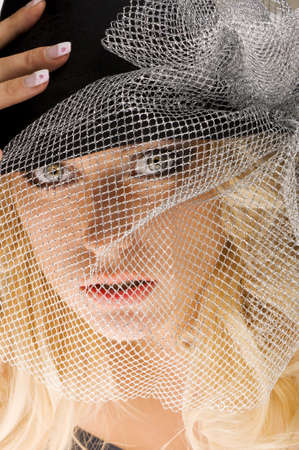 creative and nice close up beauty portrait of blond beautiful girl with silver net over her face looking in camera photo