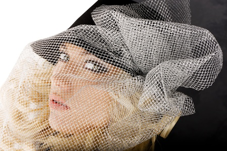 creative portrait of blond beautiful girl with hair style black hat and a silver net over her face Stock Photo - 8432725