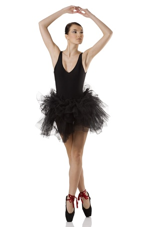 classic dancer with black dress and shoes on white background dancing on pointe Stock Photo