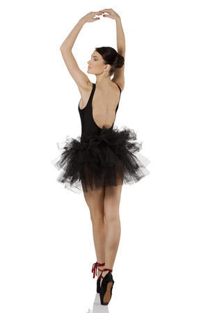 beautiful girl classic dancer with black dress and shoes on white background dancing in point photo