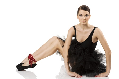 beautiful classic dancer girl sitting on white with black dress and shoes and looking in camera photo
