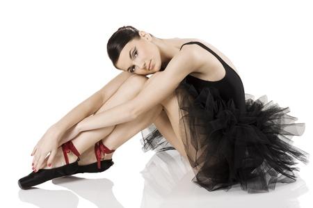 very beautiful ballerina in black tutu sitting and laying an white like a swan photo