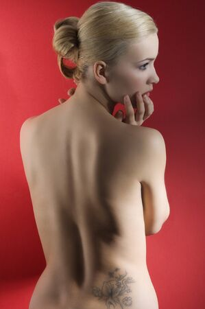 fashion elegant shot of blond naked woman with hair stylish taking pose on red background Stock Photo - 8512412