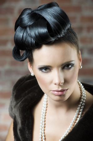 fashion portrait of a cute brunette wearing a brown fur and pearl necklace near a brick wall photo