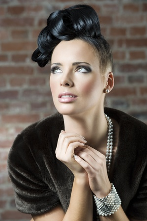 fashion close up portrait of a cute brunette wearing a brown fur and jewellery near a brick wall loking up photo