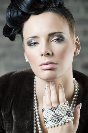 close up fashion portrait of young and beutiful girl with pearl necklace and jewellery  photo