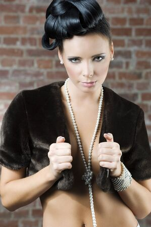 fashion portrait of a cute brunette wearing a brown fur and jewellery near a brick wall photo