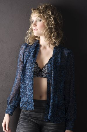 sexy blond curly haired woman in blue shirt and bra against a black wall  photo