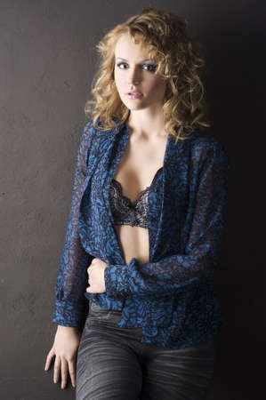 sexy blond curly haired woman in blue shirt and bra on black background  photo