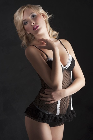 sexy shot of beautiful blond girl with red lips wearing provocative black lingerie