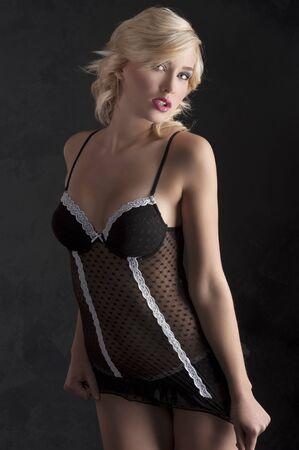 zeer sensuele jonge vrouw in sexy zwarte lingerie poseren op donkere achtergrond