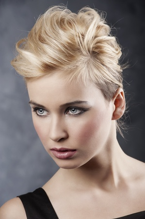 dark blond: beauty portrait of young blond girl with fashion hair style and make up on dark background