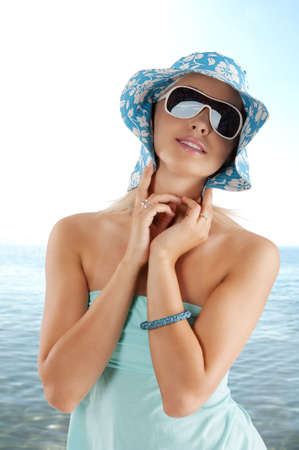 young and cute woman with sunglasses pushing hat against head  photo