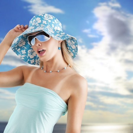 summer girl in light blue with hat and sunglasses in hot expression photo