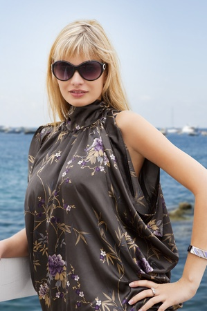 young blond beautiful woman in elegant dress and sunglasses near the sea looking in camera photo