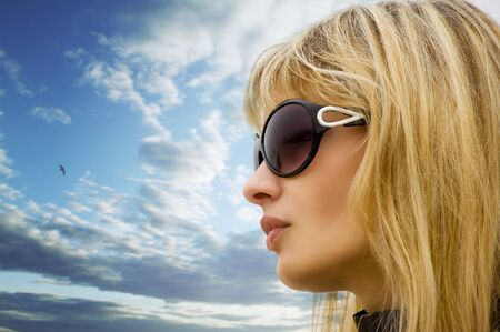 young blond beautiful woman with sunglasses against a cloudy sky photo