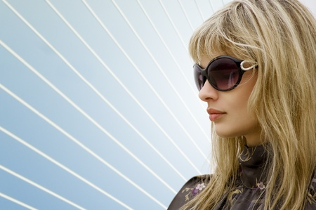 portrait of blond girl with sunglasses on the light blue background with white line photo