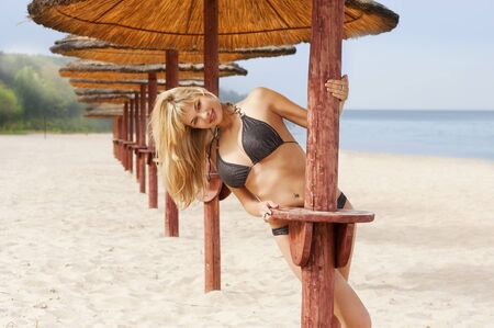 sexy and young pretty girl on the sand near some beach umbrella wearing a bikini swimwear photo