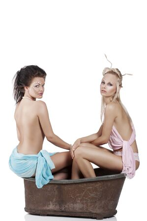 two sexy and beutiful girl half naked inside an old fashion bath with creative make up photo