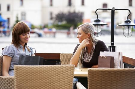Two beautiful and sophisticated young women friends sitting in a cafe outdoor photo