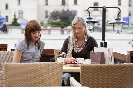 Two beautiful and sophisticated young women friends having coffee ia a city cafe photo