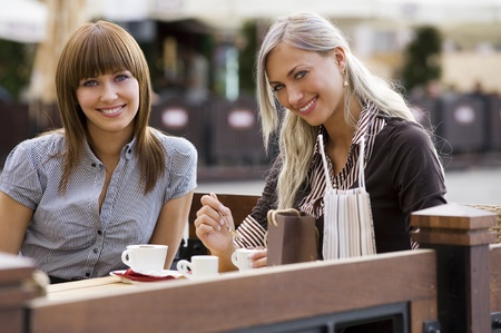 young cute elegant woman sitting outdoor in a cafe in a city with coffee and smiling photo