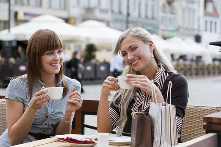 very cute smiling women drinking a coffee sitting outside in a cafe bistro  photo