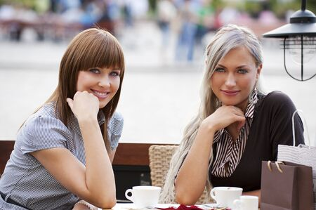 Two beautiful and elegant woman sitting outside in a cafe and looking in camera smiling  photo