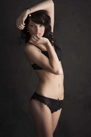 Glamorous sexy standing woman in black lingerie on black background Stock Photo - 9150607