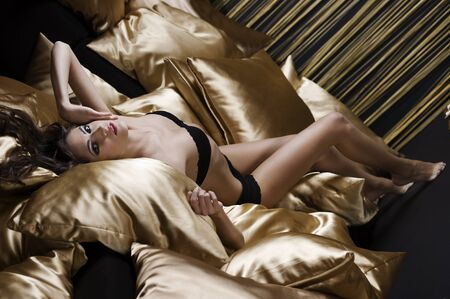 amazing shot of a young woman brunette wearing black underwear with golden pillow all around photo