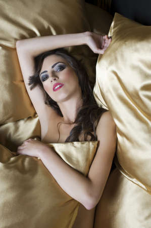 close up beauty portrait of young brunette with curly hair laying down between golden pillow photo