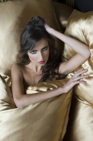 portrait of brunette between yellow pillow looking in camera in a sensual way photo