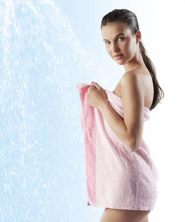 beautiful young brunette covering her naked body with a pink bath towel over white Фото со стока