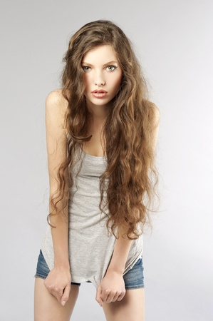 young beautiful girl with long curly hair wearing mini short jeans and looking in camera Stock Photo - 9645272