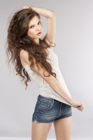 young beautiful girl with long curly hair wearing mini short jeans and posing Stock Photo - 9645271
