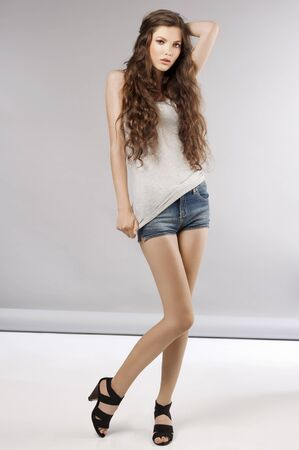 young beautiful girl with long curly hair wearing mini short jeans and posing Stock Photo - 9645256