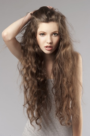long curly hair young cute girl in a porteait on gray background Stock Photo - 9645274