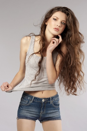 fashion shot of beautiful young woman with long curly hair in casual dress Stock Photo - 9645292