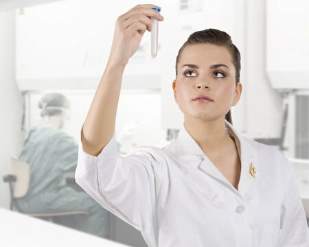 cute brunette woman in white gown as a medical doctor looking at a test tube photo