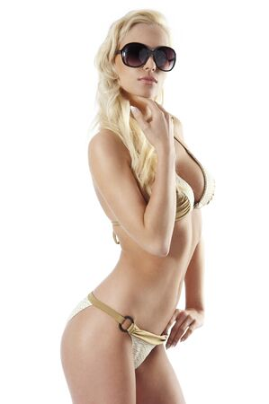 erotic girl: beautiful and sexy blond girl in bikini and sun glasses with hair style posing on white