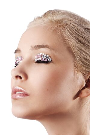 very cute blond young woman with hair style with some shining gem stone on her eyes as a creative make up photo