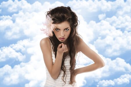 fashion shoot of a curly brunette wearing a white dress and a pink feather in her hair photo