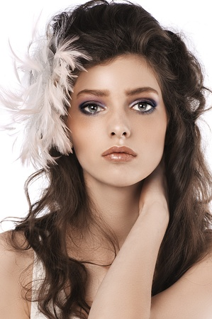 hair feathers: fashion close up of a brunette with long curled hair and pink feather accessory Stock Photo