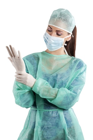 professional practice: nurse in surgery dress with cap and mask in act to dress gloves