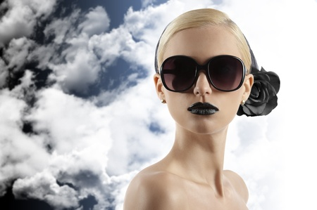 fashion portrait of young blond woman with hair style black lips and wearing sunglasses looking at the camera against white background photo
