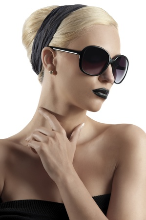 fashion portrait of young blond woman with hair style black lips and wearing sunglasses posing against white background photo