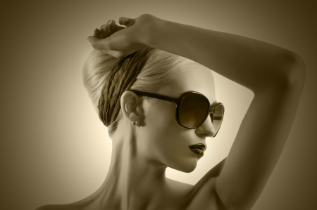 fashionable sunglasses: fashion portrait of young blond woman with hair style black lips and wearing sunglasses posing against white background