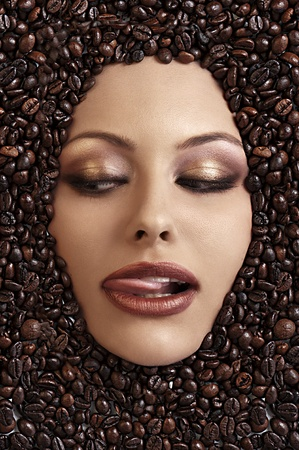 close up portrait of a girls face immersed in coffee beans sticking her tongue out photo