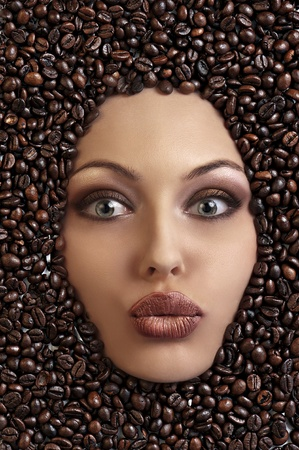close up of a girls face drowned in coffee beans blowing a kiss photo