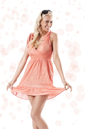 pretty young blond woman wearing a summer orange dress standing against white background holding her dress around the bubbles photo